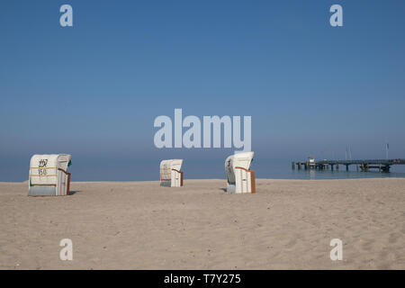 three roofed wicker beach chairs on deserted sandy beach under blue sky in Dahme Germany - Stock Photo