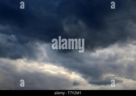 Storm sky covered with dark cumulus clouds before the rain. Dark cloudy sky, overcast day, beautiful dramatic background for stormy weather - Stock Photo