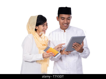 asian muslim couple wearing white using tablet  - Stock Photo