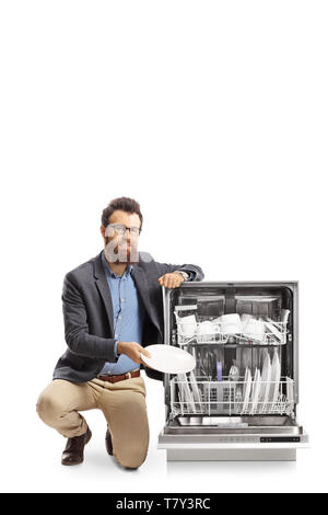 Bearded man putting a plate into a dishwasher isolated on white background