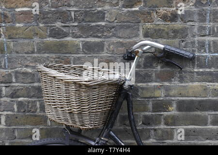 image of an old fashioned bicycle that has a wicker basket on the front propped up against a brick wall - Stock Photo
