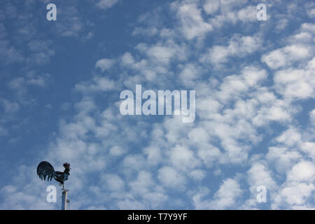 Fluffy cotton wool clouds with small weathercock in front of blue sky. - Stock Photo
