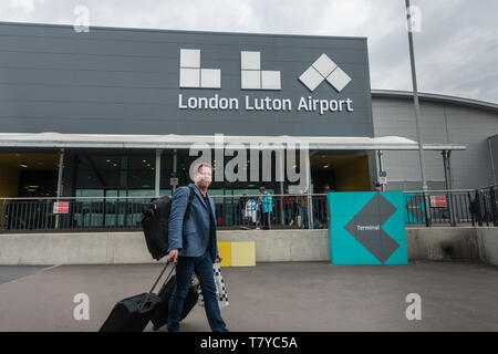 London Luton Airport new terminal building logo with male caucasian traveller wearing a rucksack and pulling two suitcases with his tongue out - Stock Photo