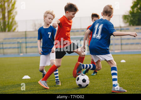 Young Football Players Kicking Ball on Soccer Field. Soccer Horizontal Background. Youth Junior Athletes in Red and Blue Soccer Shirts - Stock Photo