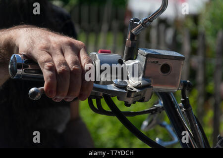 Man without gloves with his hand on the handlebars and takes the front brake - Stock Photo