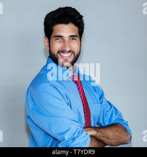 Portrait of laughing latin american hipster businessman on grey background - Stock Photo