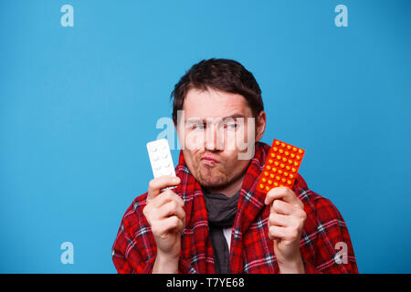 Sick man wrapped in a blanket chooses pills - Stock Photo
