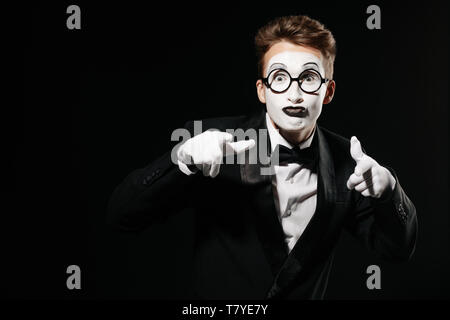 portrait of mime man in tuxedo and glasses points at you on black background - Stock Photo