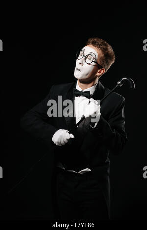 portrait of mime man in tuxedo and glasses posing with walking stick on black background - Stock Photo