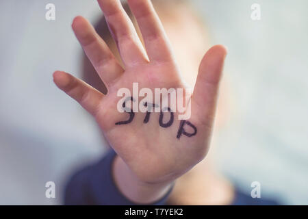 Concept of domestic violence and child abusement. A little girl shows her hand with the word STOP written on it. Children violence. - Stock Photo