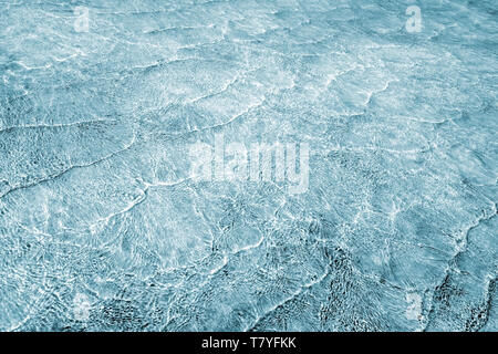 Empty abstract background naturally created by small sea waves in shallow waters and sunlight reflections on water surface. Toned in blend of turquois - Stock Photo