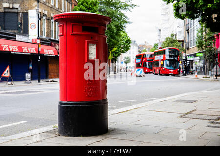 Exterior Red Royal Mail Pillar Post Box on street. Red bunk buses in the background - Stock Photo