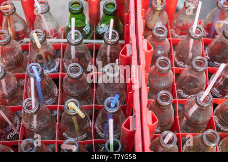 many plastic straws in the crate full of empty soft drinks (coca-cola) bottles. - Stock Photo