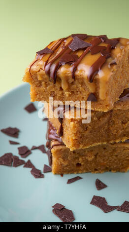 Stack of three sweet potato blondies with thin lines of chocolate and caramel icing running down at the sides and chocolate chips on teal plate, green - Stock Photo