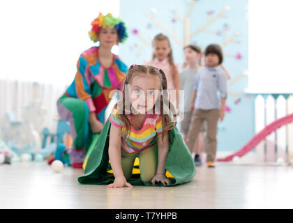 Children kids playing with clown on birthday party in entertainment centre. Little girl climbing through tunnel - Stock Photo