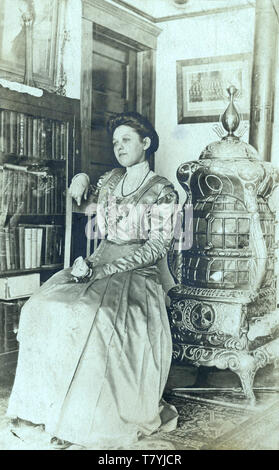 Woman in Victorian interior with cast iron room heater, ca. 1910.  New York State.  RPPC - Stock Photo