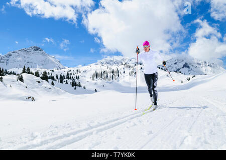 Young female skier during training session on cross-country skis, doing classical style in high alpine region - Stock Photo