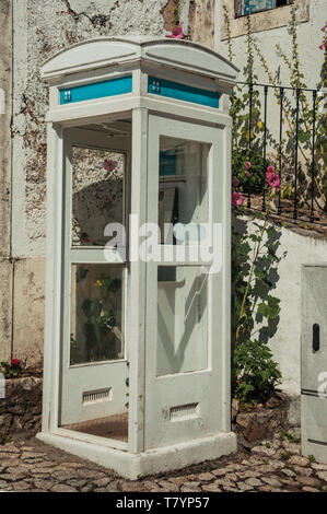 Charming painted wood telephone booth at a cobblestone alley, in a sunny day at Marvao. A medieval hamlet perched on a crag in Portugal. - Stock Photo