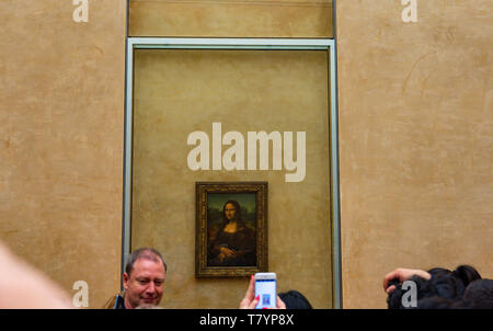 Louvre Museum Visitors Taking Pictures of Leonardo da Vinci's Mona Lisa Painting with their cameras. The painting is one of the world's most famous - Stock Photo
