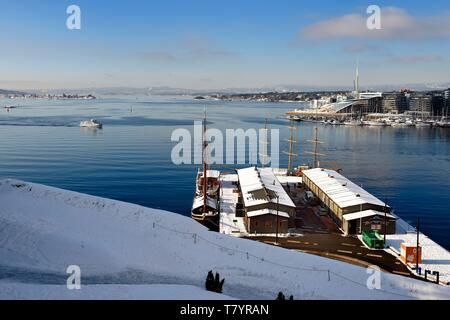 Norway, Oslo, the fjord, the harbor and the Pipervika docks seen from the Akershus hill under the snow, the Aker Brygge district in the background right - Stock Photo