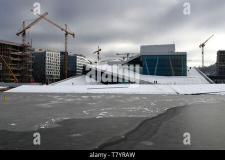 Norway, Oslo, the Opera under the snow, designed by the architecture firm Snohetta (including Tarald Lundevall) on the commercial and industrial port of Bjorvika district undergoing restructuring - Stock Photo