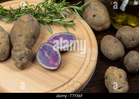 purple red  potatoes on a cutting board and old dark wooden table, rosemary, garlic and olive oil - Stock Photo
