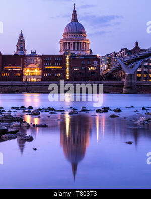 London, UK - April 1st 2019: A dusk-time view of the magnificent St. Pauls Cathedral and its reflection in the River Thames in London, UK. - Stock Photo