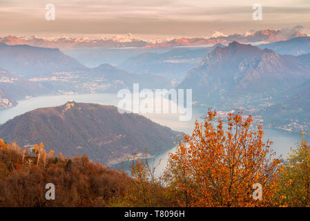 Iseo Lake, Monte Isola and Orobie Alps at sunset with fog in autumn season, Brescia Province, Lombardy, Italy, Europe - Stock Photo