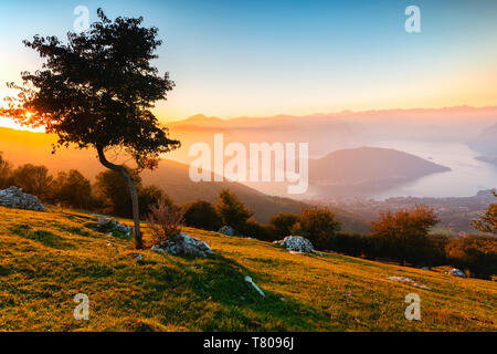 Iseo Lake and Monte Isola at sunset with fog in autumn season, Brescia Province, Lombardy, Italy, Europe - Stock Photo