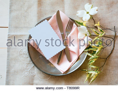 Spring Table Place Setting with white flowers, pink napkin, silverware and a blank card for party menu or invitation.  It's an above view with natural - Stock Photo
