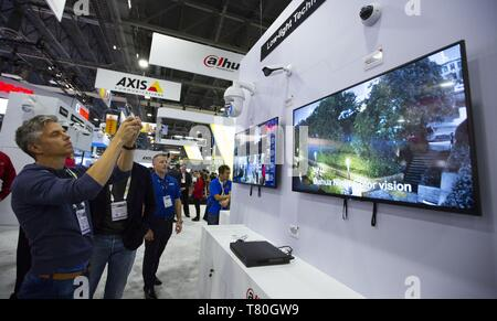 Beijing, USA. 10th Apr, 2019. A visitor takes photos at the booth of Zhejiang Dahua Technology at the International Security Conference and Exposition (ISC West) in Las Vegas, the United States, April 10, 2019. Over 3,000 exhibitors from more than 100 countries and regions will participate in the 21st China Hi-Tech Fair (CHTF) in November, 2019. Credit: Li Ying/Xinhua/Alamy Live News - Stock Photo