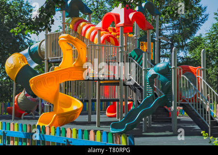 Empty playground in a city park on a hot sunny summer day. - Stock Photo