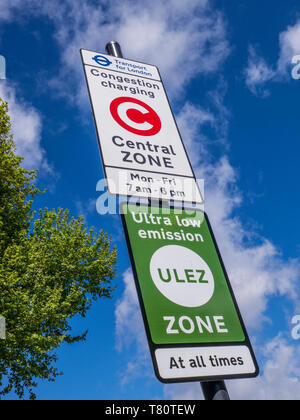 'ULEZ' TFL congestion charging central zone sign with 'ULEZ' ultra low emission zone sign against blue sky with tree in fresh green leaf London SE11 - Stock Photo