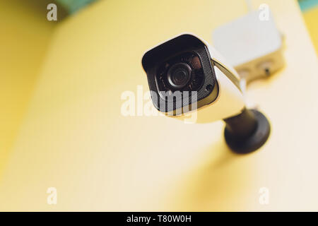 Security camera and motion detector installed on ceiling in room - Stock Photo