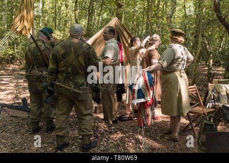 Woodhall Spa 1940s world war two festival re-enactment weekend, civilians and military personnel within a shaded woodland clearing. - Stock Photo