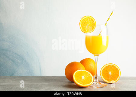 Glass with fresh orange juice and tubule, oranges on grey table against color background, space for text. Fresh natural drink - Stock Photo