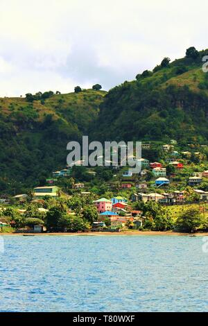 An example of the lush green hills and colorful buildings which make up the landscape of the Caribbean island of St Vincent. - Stock Photo