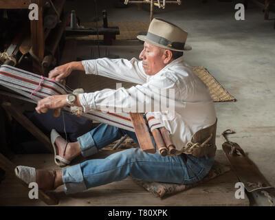 Indigenous man weaving with a backstrap loom, Otavalo, Ecuador, South America - Stock Photo