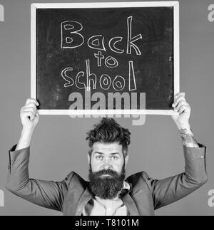 Teacher bearded man holds blackboard with inscription back to school blue background. Teacher with tousled hair stressful about school year beginning. Teaching stressful occupation. Do not be upset. - Stock Photo