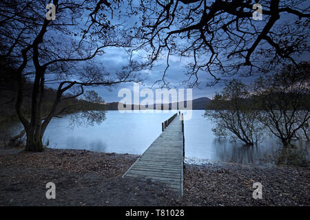 A solitary figure at dusk on Rigg Wood jetty, Coniston Water, Lake District National Park, UNESCO World Heritage Site, Cumbria, England, UK - Stock Photo
