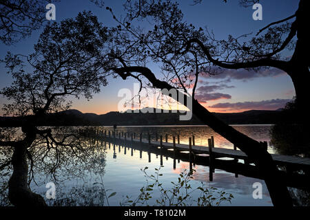 Sunset at Rigg Wood jetty on Coniston Water, Lake District National Park, UNESCO World Heritage Site, Cumbria, England, United Kingdom, Europe - Stock Photo