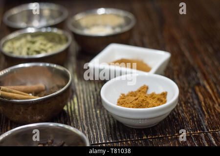 Close-up of a variety of spices in metal bowls for making Masa tea in a yoga studio - Stock Photo