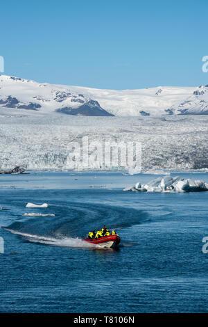Boat tour on Jokulsarlon Glacier Lagoon, with Breidamerkurjokull Glacier behind, South East Iceland, Iceland, Polar Regions - Stock Photo