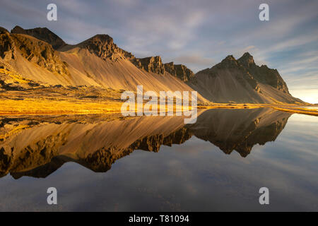 View of mountains of Vestrahorn and perfect reflection in shallow water, soon after sunrise, Stokksnes, South Iceland, Iceland, Polar Regions - Stock Photo