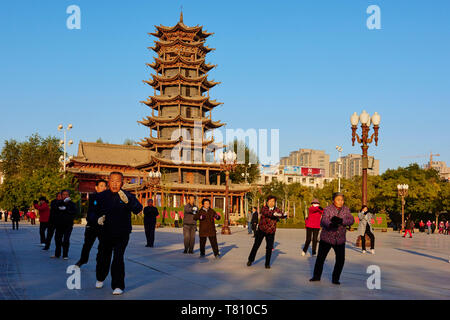 Morning exercises in front of the wooden pagoda on the main square, Zhangye, Gansu Province, China, Asia - Stock Photo