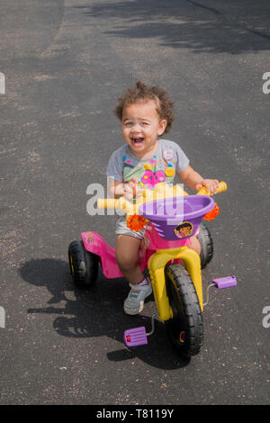 Vadnais Heights, Minnesota. One and a half year old bi-racial girl riding her three wheeler with a happy face. - Stock Photo