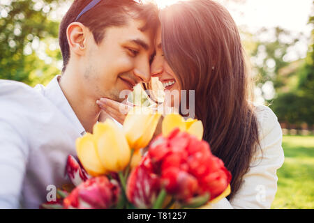 Happy young couple in love hugging with spring flower bouquet outdoors. Man gifted his girlfriend with tulips