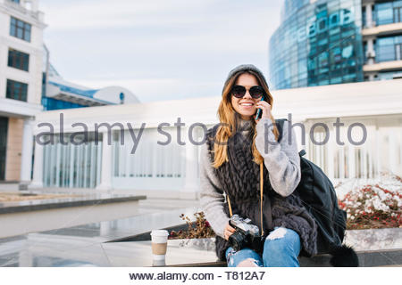 Stylish city joyful young woman sitting in Europe modern city centre, wearing winter woolen sweater, sunglasses, knitted hat. Speaking on phone, travelling with bag, camera, smiling. Place for text - Stock Photo