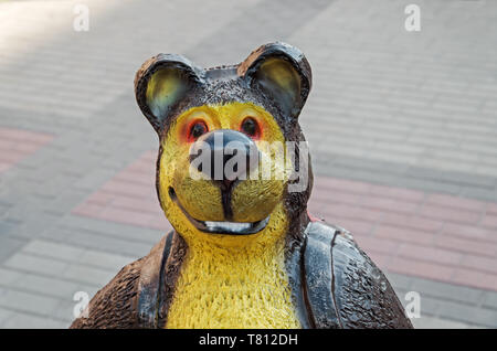 Funny and artisan bear sculpture standing in the town square - Stock Photo
