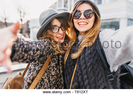 Selfie portrait of joyful fashionable girls having fun on sunny street in city. Stylish look, wearing sunglasses, having fun, travelling with friends, smiling, expressing true positive emotions - Stock Photo